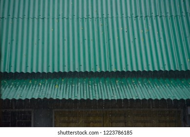 Green metallic rooftop of a house in the rain unique photo