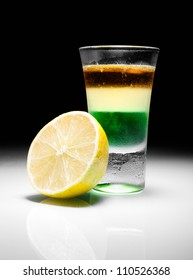 Green mexican shot cocktail with lemon slice