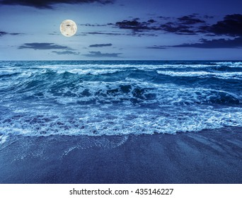 green and mighty sea wave crashes on sandy beach and break at night in full moon light