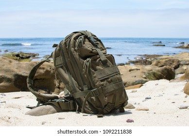 Green military backpack sitting on sandy beach with rocky ocean coastline in background on sunny day