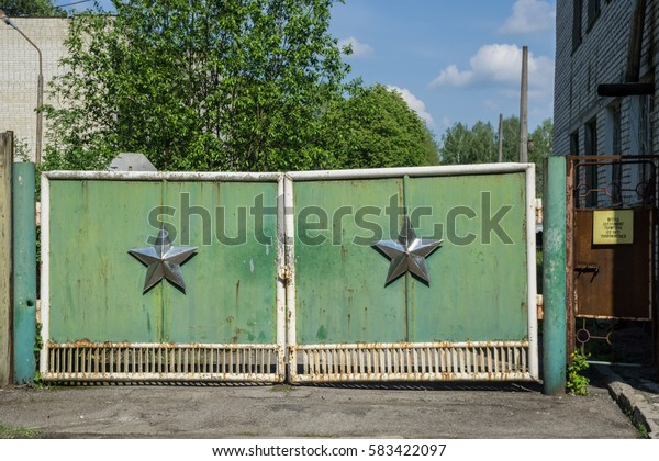 Green military gate with silver Soviet star at Chernobyl Exclusion Zone.