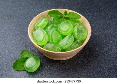 Green mint candy in a wooden bowl on a dark background