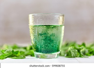 Green mint chlorophyll drink in glass with water drops on white table
