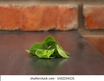 Green mint leaves on wooden table against old red brick wall