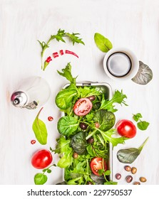Green mix salad with tomatoes,oil and balsamic vinegar on white table, top view
