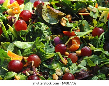 Green mixed salad full of nuts and fruit
