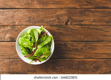 Green mixed salad with spinach, arugula and beetroot leaves in bowl on vintage wooden table with copyspace. Top view
