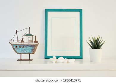 Green mock up picture frame on white shelf with small plant in a pot and wooden boat against white wall; portrait orientation; stylish interior bright background
