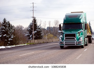 Green modern big rig semi truck with grille protection bumper transporting commercial cargo tightened with slings on flat bed semi trailer on the winter snowy road with trees on background