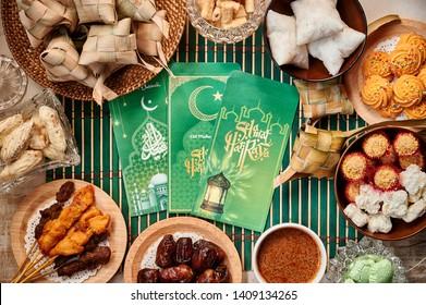 Green money packet with Eid Mubarak and Selamat Hari Raya wording. Traditional Malay Food and cookies during Ramadan and Eid Mubarak. Hari Raya Aidilfitri Festival