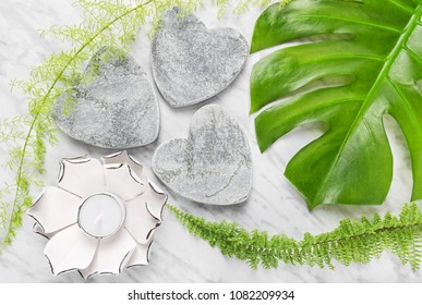 Green Monstera leaf, fern plants, stone hearts and lotus candle on marble background. Natural decor.