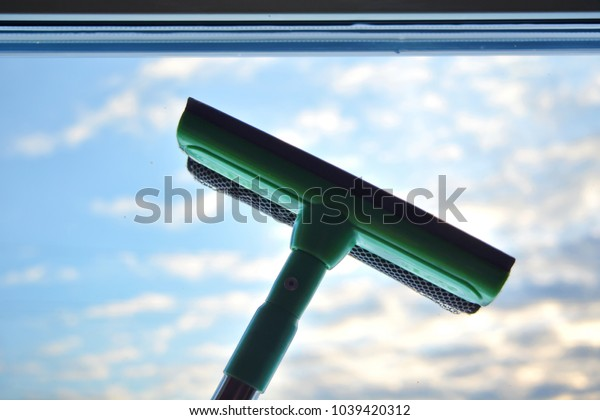 Green mop cleaning clear glass of window and blue sky with cloud background