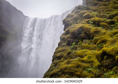 The green mossy cliffs next to the Skogafoss waterfall in Iceland.
