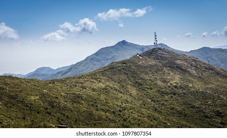 Green mountain with an antenna at the top surrounded by higher mountains and beautiful blue sky