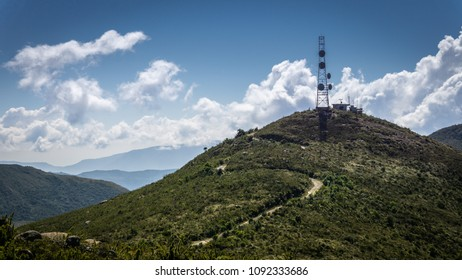 Green mountain landscape with an antenna tower at the top and a road. In the background, mountains with green nature and blue sky in Brazil.