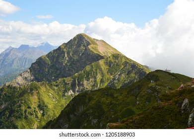 green mountain peaks centered on a large space under the clouds on a sunny summer day