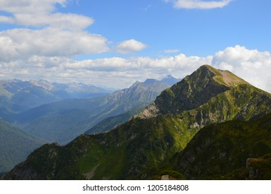 Green mountain peaks shifted to the right in a large space under the clouds on a sunny summer day