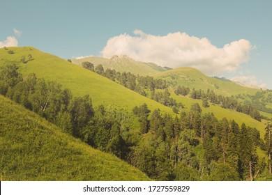 green mountain ridge under a cloudy sky, green hill slope outdoor scene