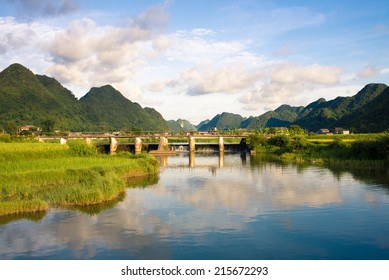 Green mountainous range with a clear river as foreground with the reflection of the blue sky of Bac Son Valley in Vietnam