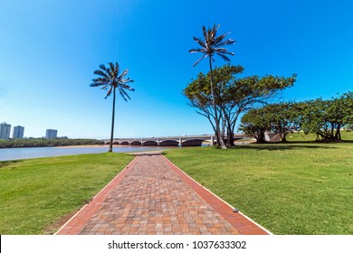 Green mowed lawn and paved walkway at Umgeni river estuary against bridge and clear sky at Blue Lagoon in Durban, South Africa