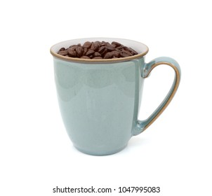 Green mug filled with dark roasted coffee beans, standing on a white background