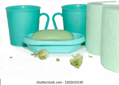 green mugs, two rolls of toilet paper and soap closeup
