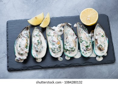 Green mussels served with cheese sauce and lemon on a stone slate tray over grey concrete background