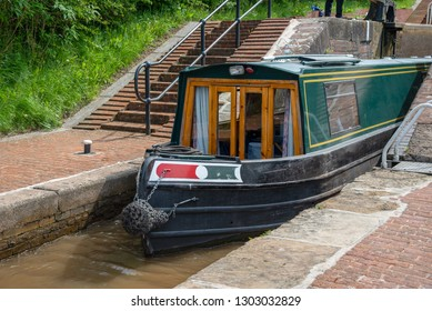 Green narrowboat leaves the middle lock chamber of the Lock on the LLangollen Canal.