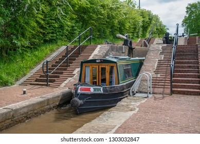 Green narrowboat leaves the middle lock on the LLangollen Canal.