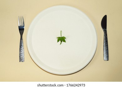 Green nature background. A green cannabis leaf on top on a cream color plate, knife and fork. On a beige background. Flat lay, copy space.