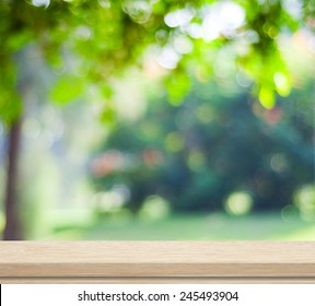 Green nature background, Empty wooden deck table over blur tree garden park with bokeh in spring summer outdoor background, Wood shelf, counter, desk surface for food picnic, product display montage