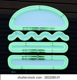 A green neon sign in the shape of a hamburger