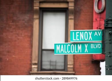green new york street sign: Malcom X and Lenox