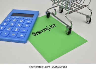 A green note paper is written the word grocery list with a small trolley and a calculator in blue.