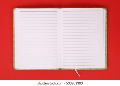 Green notebook isolated on red background with soft shadow, place for your text