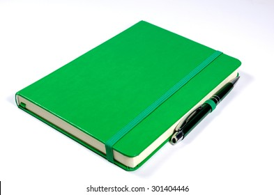Green notebook and pen isolated on white background
