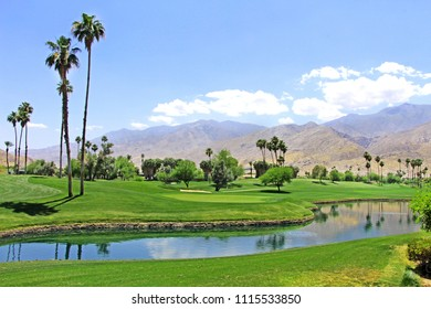 Green oasis in the desert - Golf course with palm trees and pond in Palm Spring, California on March 31, 2018