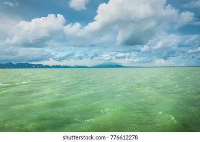 Green ocean water with blue cloudy sky on the background