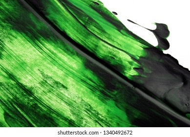 Green Oil paint brush strokes in green on white canvas area with copyspace area for art based designs and backgrounds