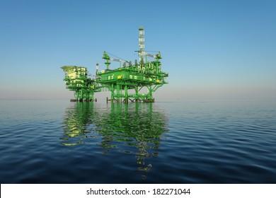 green oil rig platform on calm blue sea