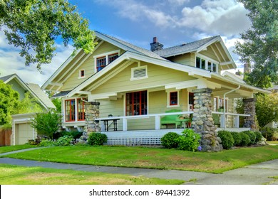 Green old craftsman style home with covered porch in the summer.