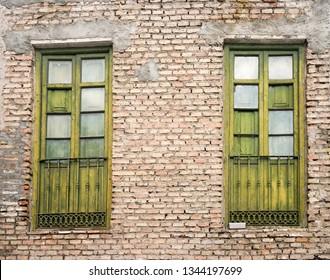 green old windows on brick wall