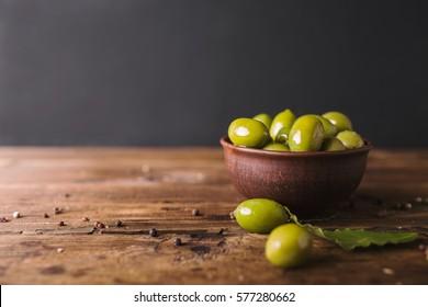 Olives vertes, feuille de laurier sur fond bois.