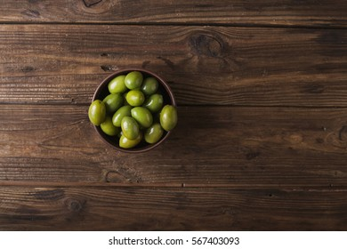 Green olives in a ceramic bowl on a wooden background.