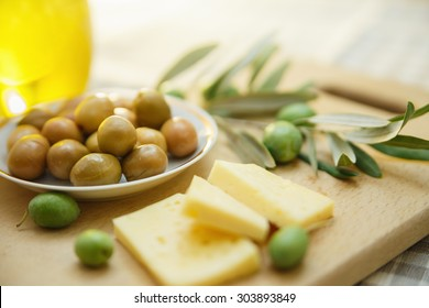 Green olives with cheese and olive branch on a wooden board