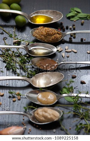 Green olives, fresh herbs, apple wedge, seeds, pepper, seeds, garlic with condiments and ingredients in spoons arranged in a line on a black background, side view