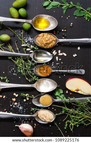 Green olives, fresh herbs, apple wedge, seeds, pepper, garlic with condiments and ingredients in spoons arranged in a line on a black background, top view