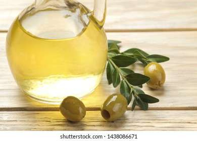 Green olives with leaves and olive oil on a natural wooden table. close-up. place for text.