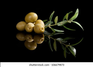Green olives with olive branch isolated on black background. Culinary traditional appetizer.