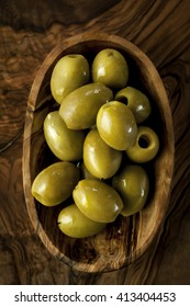 Green olives with olive oil drops on the oil wood board. Organic food. Olive tree wood. Dark scene.